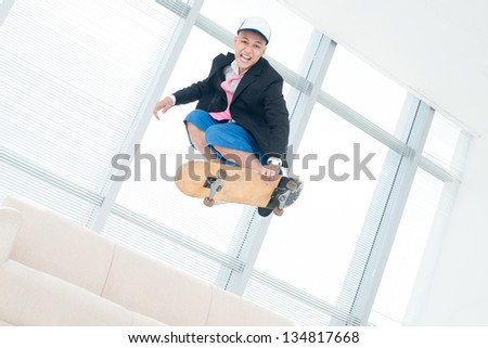 Funky guy performing a stunt jumping high on skateboard - stock photo