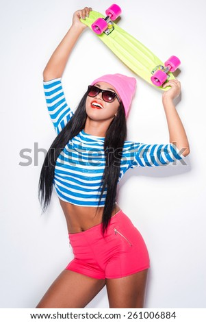 Funky skater girl. Playful young African woman in funky clothes carrying colorful skateboard and smiling while standing against white background - stock photo