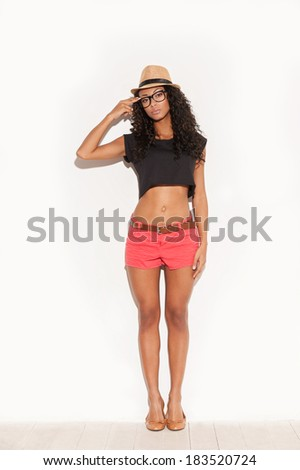 Funky style. Full length of beautiful young African woman in glasses and funky wear gesturing and looking at camera  - stock photo