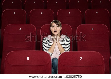 Funky woman watching a movie alone at the cinema - stock photo