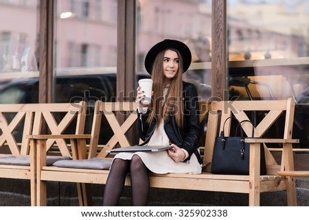 Funky woman with cool style holding closed net-book on her knees while sitting on a cozy bench near coffee shop window, young hipster girl enjoying c while resting after work on laptop computer - stock photo