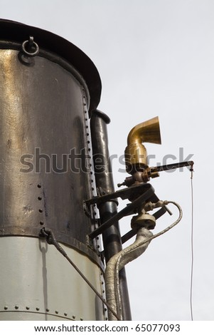 Funnel and whistle from a steamship against a grey sky - stock photo