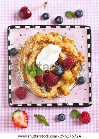 Funnel cakes with fresh berries and whipped cream - stock photo