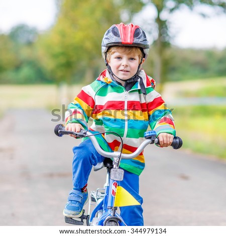 Funny active little boy riding on bicycle on warm summer day. Countryside. Child in helmet. Active leisure and sports for kids.