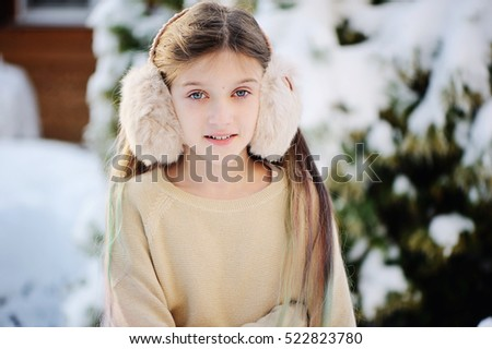 Funny adorable little girl in gold sweater and fur headphones having fun in beautiful winter park