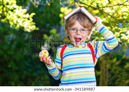 Funny adorable little kid boy with glasses, books, apple and backpack on his first day to school or nursery. Child outdoors on warm sunny day, Back to school concept