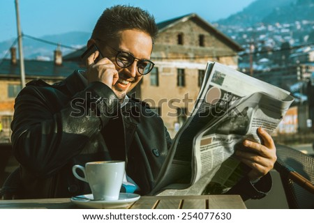 Funny adult male read newspaper talking phone and drinking coffee outdoors - stock photo