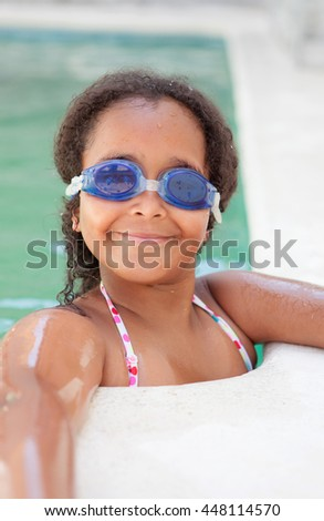 Funny afroamerican girl with goggles cooling off in the pool