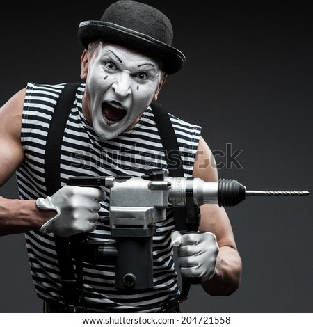 funny aggressive mime holding puncher - stock photo