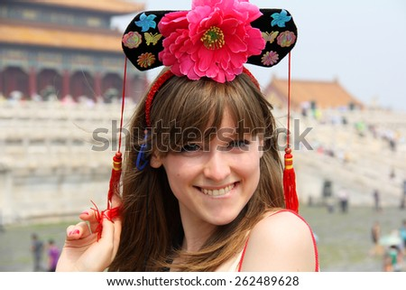 Funny and Attractive Young Woman in Forbidden City in Beijing Smiles with Traditional Chinese Hat on Her Head - stock photo