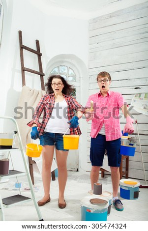 Funny and crazy terrified young couple with paint cans in their hands and paint  brush doing repair at home. White background