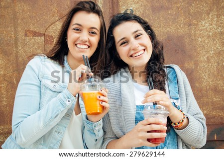 Funny and cute girls having a fruit smoothie in the street - stock photo