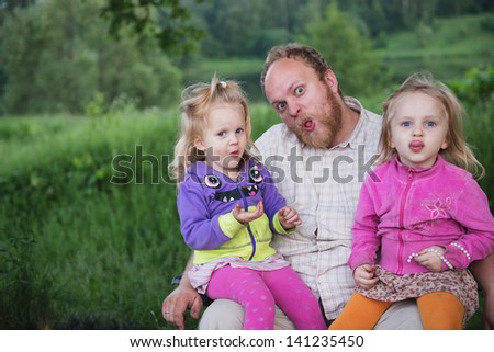Funny and happy father and daughters making faces together - stock photo