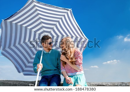 Funny and young couple have fun with beach umbrella on the roof on blue sky background - stock photo