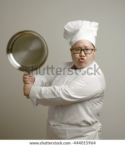 funny asian chef holding iron pan over grey background - stock photo