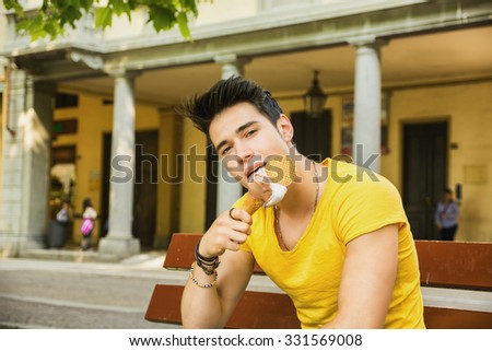 Funny attractive young man sitting, wearing yellow T-shirt while eating a tasty vanilla ice cream outdoors in the park, in a warm day of summer - stock photo