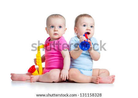 Funny babies girl and boy  play musical toys isolated - stock photo