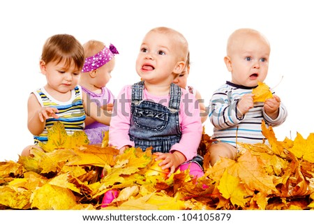 Funny babies group sit in yellow leaves