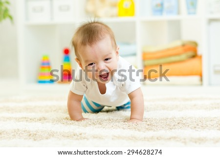 funny baby boy crawling on carpet at home - stock photo