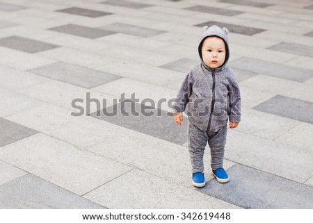 Funny baby boy in bear costume suit stands on a street pavement looking at camera. Gray pavement on background. Bear hood. Copy space. Baby fashion and loneliness concept. Mixed asian-caucasian race - stock photo