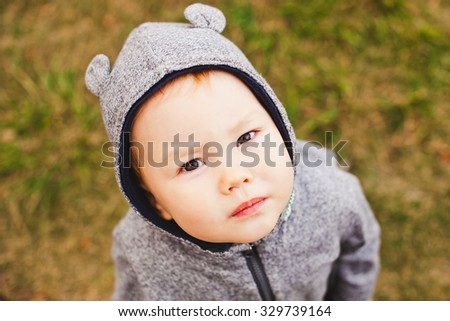 Funny baby boy in bear costume suit with bear ears on hood looks at camera from bottom with distrust. Brown grass background. Copy space. Overhead view from the top. Mixed race appearance - stock photo