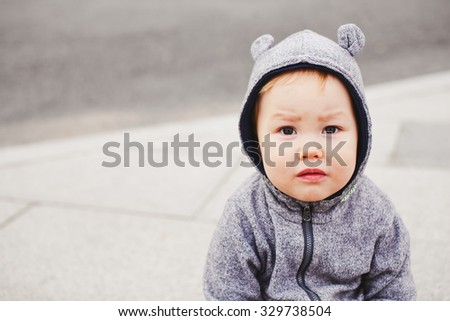 Funny baby boy in bear costume suit with ears looks at camera with grey pavement stones on background. Copy space. Baby fashion and loneliness concept. Mixed race - stock photo