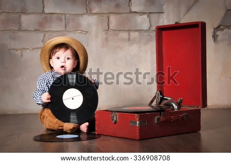 Funny baby boy in retro hat with vinyl record and gramophone - stock photo