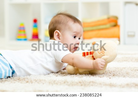 funny baby boy lying with plush toy - stock photo