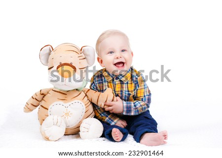 funny baby boy lying with plush toy. Smiling sitting baby boy on white background. Studio - stock photo