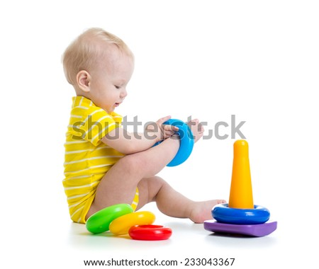 funny baby boy playing with colorful toy pyramid