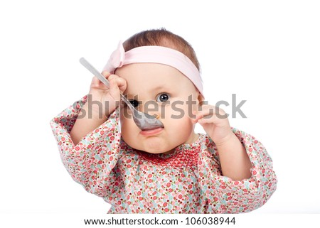 Funny baby girl eating with spoon, isolated over white - stock photo