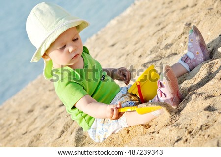 funny baby girl is playing in sand