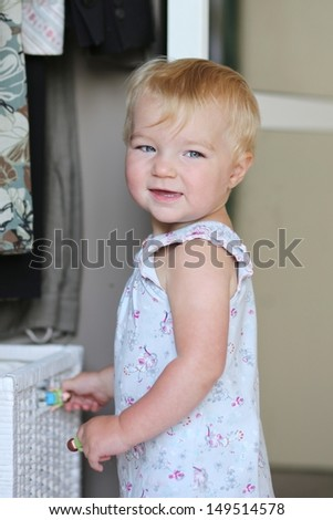 Funny baby girl is playing with white storage basket in a white wardrobe - stock photo