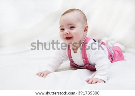 funny baby girl lying on white and smile - stock photo