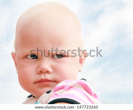 Funny baby girl outdoor summer close up portrait above cloudy sky - stock photo