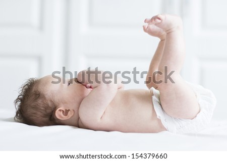 Funny baby girl relaxing in a diaper on a white blanket with her feet up in the air - stock photo