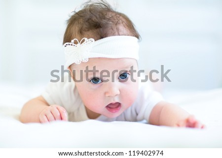 Funny baby girl with a white bow - stock photo