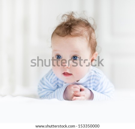 Funny baby girl with beautiful blue eyes playing on her tummy in a white nursery - stock photo