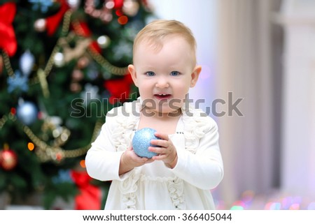 Funny baby girl with gift boxes near  Christmas tree on bright background
