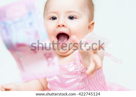 Funny baby girl with open mouth try to catch banknote