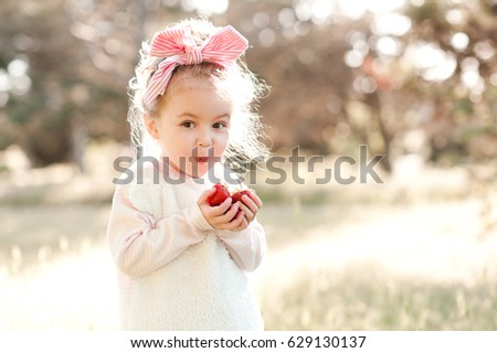 Funny baby girl 4-5 year old eating berries outdoors. Looking at camera. Childhood. Summer time.