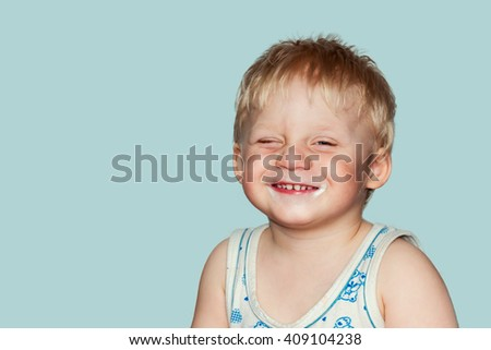 Funny baby grimaces. Studio photography on a blue background. - stock photo