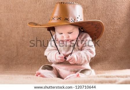 Funny baby in a big cowboy hat - stock photo