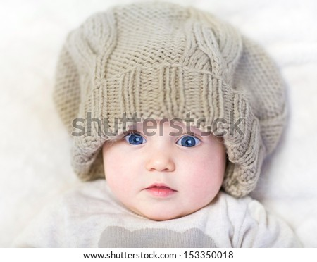 Funny baby in a huge knitted hat wearing a warm sweater relaxing on a white blanket - stock photo