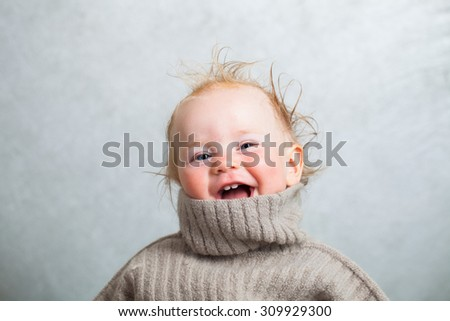 funny baby in a warm sweater - stock photo