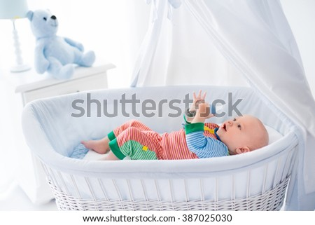 Funny baby in colorful pajamas with bottle drinking water or milk in white crib with canopy. Healthy nutrition for kids. Nursery interior and bedding for infant. Children drink formula in bed.  - stock photo