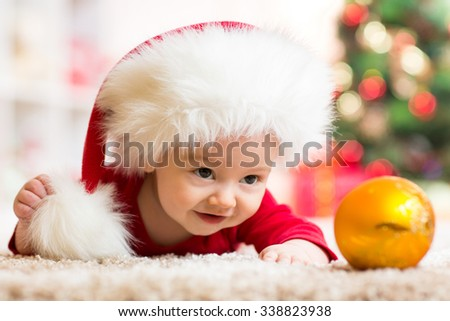 Funny baby in Santa Claus clothes with christmas tree on background - stock photo