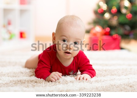 Funny baby in Santa Claus clothes with xmas tree on background - stock photo