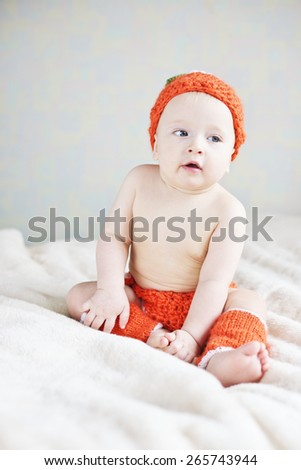 funny baby is wearing costume of pumpkin - stock photo