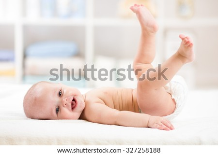 Funny baby kid weared diaper lying on bed with legs up - stock photo